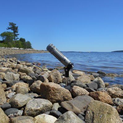 WERU.org website background, a mic nestled in ocean rocks with the ocean behind it